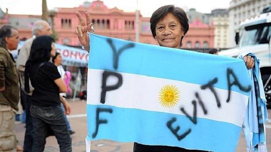 AFP; flaga Argentyny, a na niej wypisane dwa narodowe symbole - Evita i naftowy gigant YPF